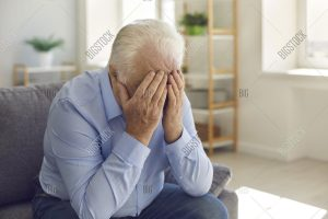 Elderly man with head in hands feeling like a burden to his caregiver in Rochester, NH.