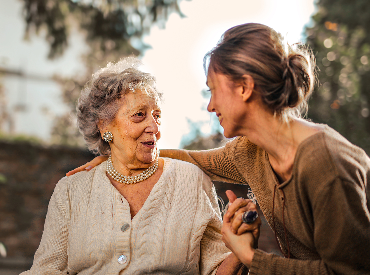 Picture of mother and daughter outdoors Woman offering caregiving support to elderly parent in Rochester, NH.