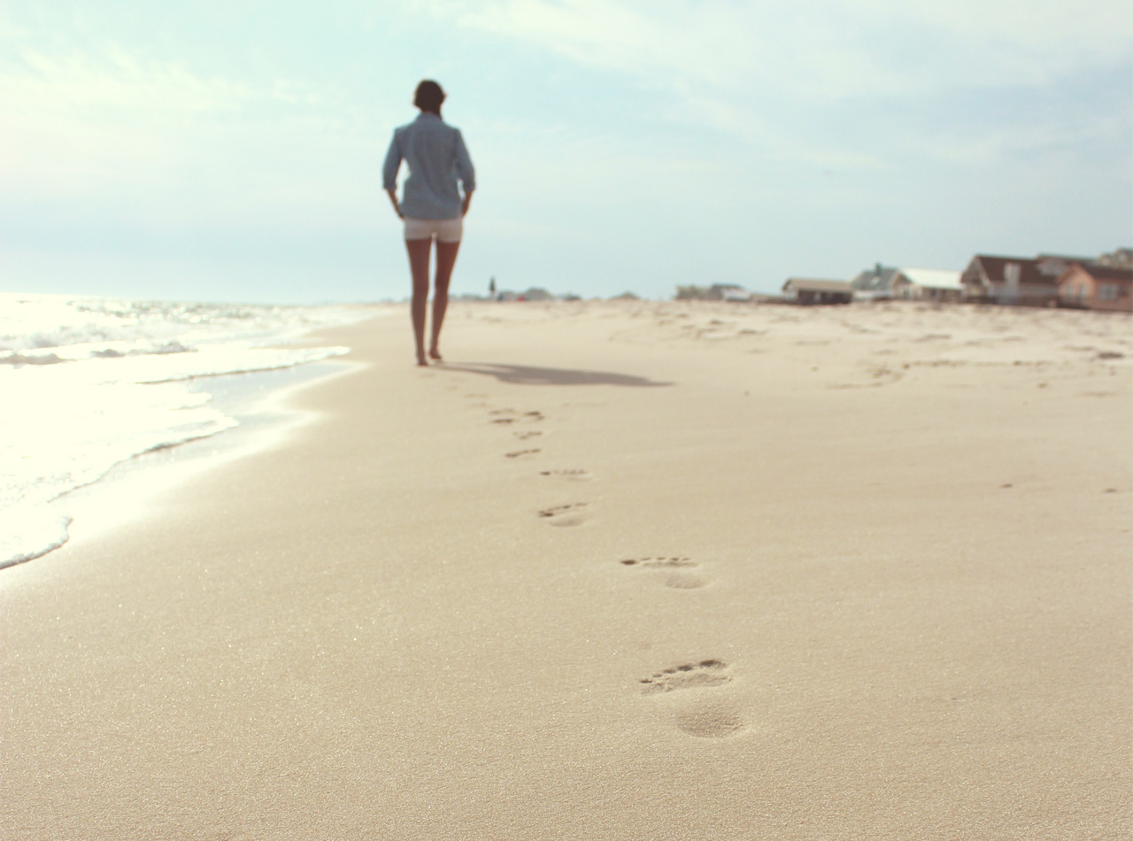 Picture of woman walking alone on the beach taking a break from her caregiver responsibilities near Dover, NH.